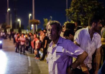 People wait outside the Ataturk airport in Istanbul, where dozens have died in an attack on Tuesday.