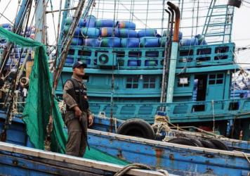 A police officer inspects a fishing boat in Thailand.