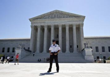 In this June 20 photo, a police officer stands in front of the Supreme Court in Washington as the court announces several decisions.