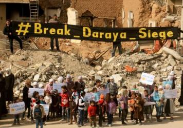 Syrian women and children stage a protest against the government's siege of Daraya, outside Damascus, on March 9. The protesters demanded that President Bashar Assad's government allow humanitarian aid into the city.