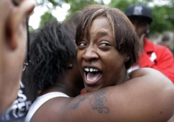 Diamond Reynolds, the girlfriend of Philando Castile, is consoled as she talks about his shooting death with protesters and media outside the governor's residence in St. Paul, Minn.