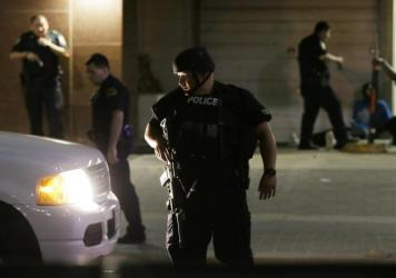 Dallas police detain a driver after several police officers were shot Thursday evening in downtown Dallas. Snipers shot police officers — killing several — during a peaceful protest, the city's police chief said at a news conference.