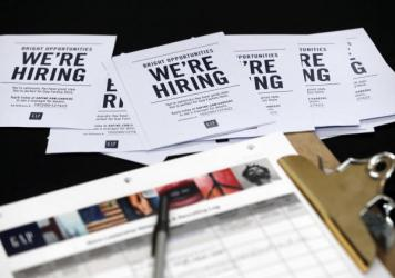 Job applications and information for the Gap Factory Store sit on a table during an October job fair at Dolphin Mall in Miami.