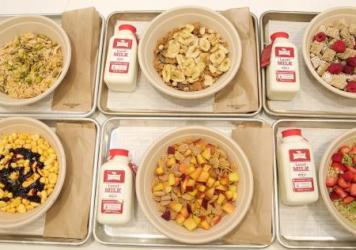 After customers order at Kellogg's NYC, they are handed a buzzer that corresponds to a number on a door designed to look like a kitchen cabinet. Behind the door, a brown paper bag awaits with a bowl of cereal and an individual-sized container of milk.