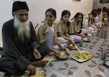 Pakistan's most renowned humanitarian, Abdul Sattar Edhi (left), shares a meal with children living in one of his charity houses in Karachi. Edhi died Friday at age 88.