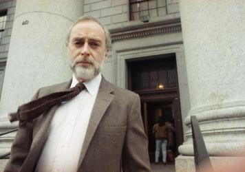 Journalist Sydney Schanberg poses for photographers after speaking to reporters in New York in 1991.