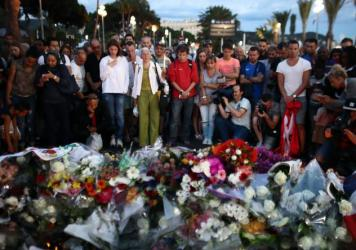 People gather and lay flowers on Nice's Promenade des Anglais on July 15. A French-Tunisian attacker left 84 people dead after driving a truck through crowds gathered to watch fireworks during Bastille Day celebrations. The attacker then opened fire on t