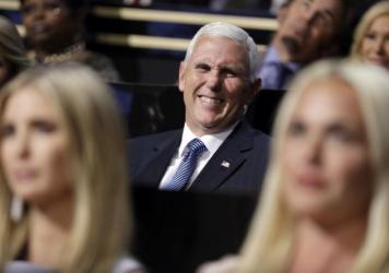 Vice presidential nominee Gov. Mike Pence of Indiana smiles as he sits during the second day session of the Republican National Convention in Cleveland on Tuesday.
