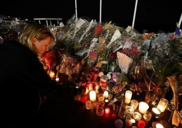 A woman lights a candle on Monday in Nice, France, near a makeshift memorial for the victims of the deadly Bastille Day attack.
