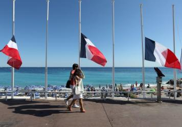 """French flags are seen lowered at half-mast in Nice on July 16. The truck attack on July 14 killed 84 people. """"I felt coming to celebrate on holiday and people are in mourning didn't seem right,"""" one vacationer says. """"But I'm glad I came."""""""