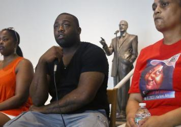 Delrawn Small's companion Zaquanna Albert, left, and his brother Victor Demsey, center, and Cynthia Howell, right, an advocate with Families United for Justice, an organization made up of families affected by police killings, attend a news conference Thu