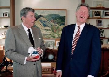 U.S. President Bill Clinton, right, reacts as former President Ronald Reagan presents him with a jar of red, white and blue jelly beans.