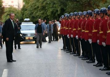 Turkey's President Recep Tayyip Erdogan (in suit and green tie) inspects a police honor guard as he arrives at the parliament in Ankara on Friday. A July 15 coup attempt was quickly crushed in Turkey, a country that has had multiple military takeovers in the past.