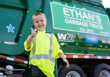"Dean rode in a green garbage truck that had a sign saying ""Ethan's Garbage Truck"" as part of a parade organized by the Make-a-Wish Foundation and local sponsors."