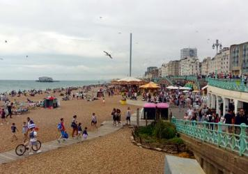Despite cloudy weather, beaches are packed in Brighton, England. With airfares rising and the British pound down after the Brexit vote, some Britons are vacationing closer to home.