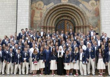 Russian Olympians, along with coaches and other officials, pose outside the Assumption Cathedral in Moscow on Wednesday before heading to Brazil. Russia had planned to send nearly 400 athletes to the Rio Games, but more than 110 have been banned because