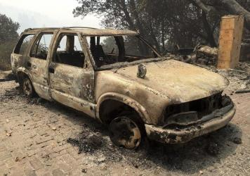 A car destroyed by the Soberanes fire in Big Sur, Calif. Lodge managers and cafe owners there are facing cancelled bookings after fire officials warned that crews will likely be battling the fire for another month.
