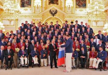 Russian President Vladimir Putin (front and center in dark suit) meets the country's Paralympic team in Moscow after it returned from the London Paralympic Games in 2012. The International Paralympic Committee plans to announce Sunday whether Russia's pa