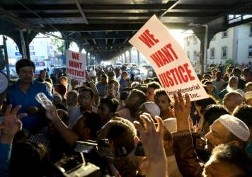 People gather for a demonstration Saturday in the Queens borough of New York, near a crime scene after the leader of a New York City mosque and an associate were fatally shot as they left afternoon prayers.