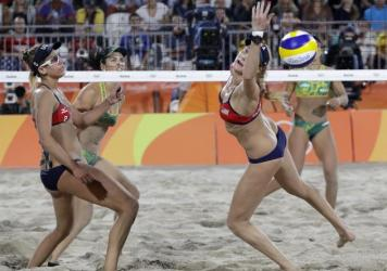 April Ross (left), watches her U.S. teammate Kerri Walsh Jennings try to reach the ball during a women's beach volleyball semifinal match early Wednesday. The Americans lost in straight sets to the Brazilians, 22-20 and 21-18, ending Walsh Jennings' quest for a fourth straight gold.
