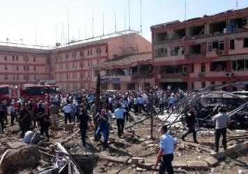 Turkish authorities search outside a damaged building after an explosion in Elazig, eastern Turkey, on Thursday. Two car bombings targeted police stations in Turkey, killing a number of people and wounding hundreds, officials said.