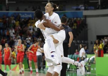 U.S. basketball player Diana Taurasi (right), leaps into the arms of teammate Angel McCoughtry as they celebrate their 101-72 win over Spain in the gold medal game on Saturday.
