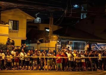 Residents stand behind a police line, observing the two dead bodies of alleged drug dealers following a drug bust operation that turned into a gunfight last month in Manila, Philippines. Nearly 1,800 people have died, police said, since the government launched a crackdown on illegal drugs after Rodrigo Duterte won a landslide presidential election victory in May with a vow to kill criminals.