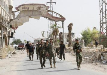 Syrian soldiers walk at the entrance of Daraya, a besieged Damascus suburb, on Friday.