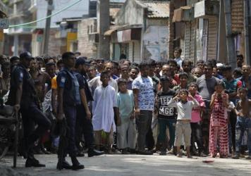 Bangladeshis gather near the scene of the raid Saturday in Narayanganj, on the outskirts of Dhaka.