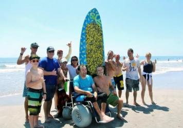"It took a team of delighted friends and family to help Florida engineer Matt Bellina (center) get back on his surfboard this summer after his severe spinal injury. The result? ""I feel like I'm home,"" Bellina said."