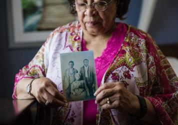 Patricia Bayonne-Johnson holds a photo of her great-grandparents and their son. The retired science teacher discovered that some of her ancestors were sold by the Jesuits of the Maryland Province in 1838, to pay off Georgetown University's massive debt.