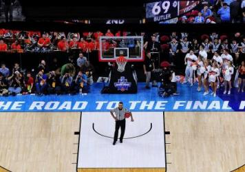 An official and others wait for play to resume between the Butler Bulldogs and the Virginia Cavaliers during a second-round NCAA men's tournament game in March in Raleigh, N.C. This coming spring, the road to the Final Four won't go through North Carolin