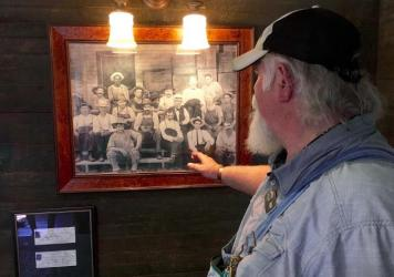 Tour guide Ron Craig points to a photo in Jack Daniel's old office at the whiskey maker's distillery in Lynchburg, Tenn. The photo, taken in the 1890s, shows Jack Daniel (wearing a black-banded white hat and a gray goatee), seated next to an African-American man. He and a second African-American man (top left) are believed to be sons of Nearis Green, who may have helped teach Daniel his trade.