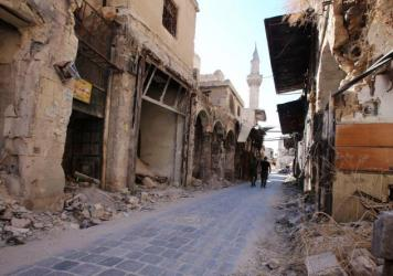 Syrian government soldiers walk in the damaged government-held side of Aleppo on Sept. 16. Initially, U.N. officials had observed calm in war-ravaged Aleppo during the recent cease-fire, but Saturday's violence in the country's eastern regions spells ill news for the truce.