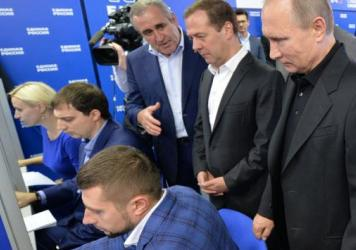 Russian President Vladimir Putin and Russian Prime Minister and United Russia party chairman Dmitry Medvedev visit the party's election campaign headquarters during parliamentary elections.