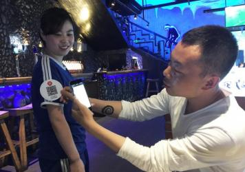 Beijing-based restaurateur Song Ji (right) demonstrates his system, which allows customers to tip waitstaff. Diners use smartphones to scan QR codes that the waitstaff wear on their sleeves. This generates a tip of 4.56 yuan, or about 70 cents. Waitress Liu Enhui (left), the top tip-getter at the restaurant, says she can earn up to $30 a day in tips.