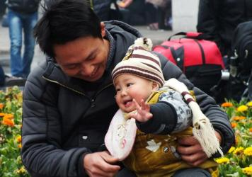 A photo from November 2013 shows a man playing with his child at a park in Yichang, in central China's Hubei province. City leaders are encouraging couples to have two children.