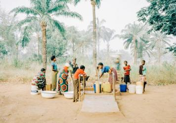 Women and children gather at a hand pump in Osukputu, Nigeria, which provides clean water for a community of around 800 people.