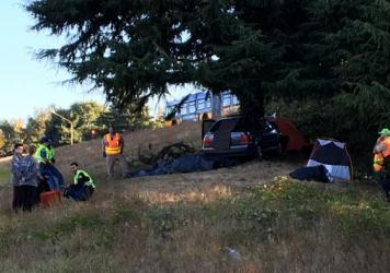 """Officials inspect the scene at the Seattle homeless camp known as """"the Jungle,"""" where a car ran off the road and resulted in the death of a young man who was in his tent."""