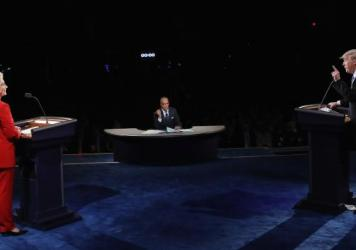 Republican presidential nominee Donald Trump speaks as Democratic presidential nominee Hillary Clinton and moderator Lester Holt listen during Monday night's presidential debate at Hofstra University in Hempstead, N.Y.