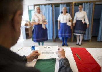 Hungarian women wearing traditional costume cast their ballot at a polling station in Budapest, Hungary, during a referendum on Oct. 2 on refugee resettlement.