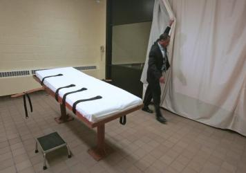 Larry Greene, public information director of the Southern Ohio Correctional Facility, demonstrates how a curtain is pulled between the death chamber and witness room at the prison in Lucasville, Ohio.