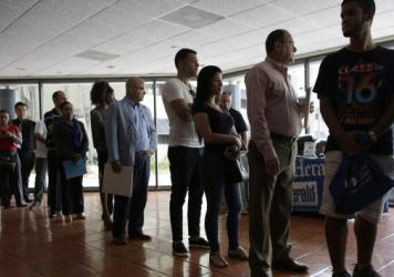 People stand in line to register for a job fair in Miami Lakes, Fla. A new study shows a growing number of young people in developed countries are giving up on work, school and training.