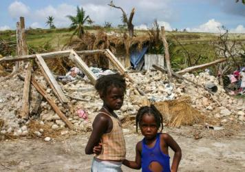 Girls stand in front of their destroyed home in the Dumont section of Port Salut. They're now living in the thatched shack that's directly behind the rubble of their home.