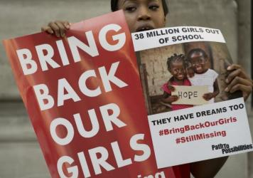 Protesters outside the Nigerian High Commission in London hold up placards demanding help from the Nigerian government to find missing girls a year after their kidnapping by Islamic extremists in April 2014.