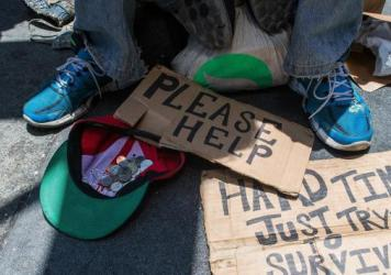 Andrew Loy begs along a sidewalk in San Francisco, Calif. on June 28, 2016.