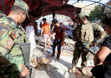 Iraqi soldiers and civilians inspect the damage at the site of a suicide bombing that targeted Shiite Muslims on Saturday in the Shaab area of the Iraqi capital Baghdad.