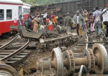 Passengers escape the site of a train derailment in Eseka, Cameroon, Friday. The death toll in the crash rose to more than 70 people Saturday, Cameroon's president says.