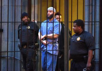 Officials escort <em>Serial</em> podcast subject Adnan Syed from the courthouse on Feb. 3 following the completion of the first day of hearings for a retrial in Baltimore. A judge granted the new trial — and now Syed has requested that he be released on bail while he waits for the retrial.