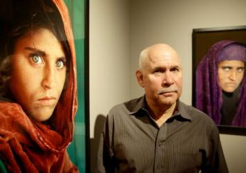 """Sharbat Gula, subject of the famous """"Afghan Girl"""" image, is in a Pakistani jail over alleged ID fraud. In 1984, Gula's brief encounter with photographer Steve McCurry, seen here next to images of Gula, led to a cover photo for <em>National Geographic</em>."""